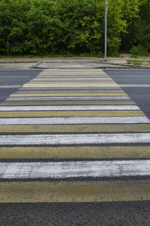Crosswalk with white and yellow stripes