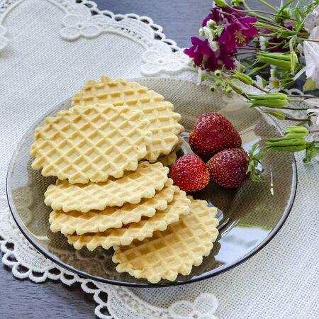 Waffles with strawberries on a black plate Zdjęcie Seryjne