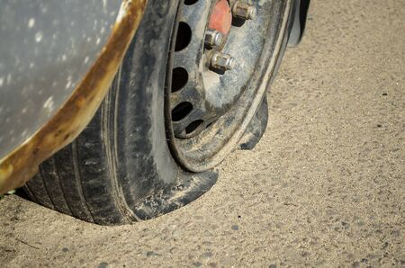 Flat tire in an old car standing on the sand