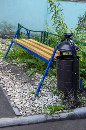 A backless bench with blue metal legs and a bin. Zdjęcie Seryjne