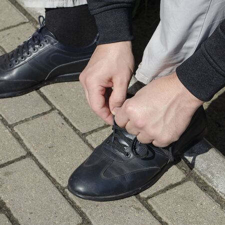 on the street A man is tying cords on leather black boots