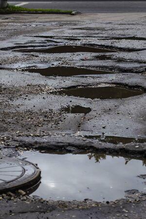 Poor condition of the road surface. Hole in the asphalt, risk of movement by car, bad asphalt, dangerous road, potholes in asphalt.