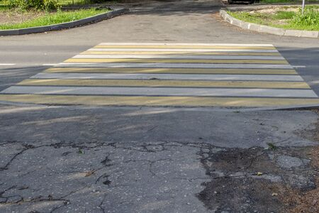 Crosswalk across the road with yellow and white stripes