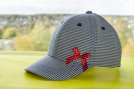 baseball cap with white and blue stripes and a red bow on a yellow background