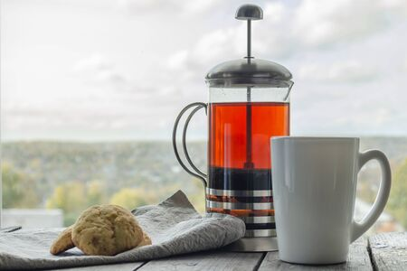 Glass teapot with tea, a white mug and homemade cookies on the background of an autumn cloudy view from the window