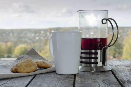 Red tea in a teapot, white mugs and homemade cookies on a table against the sky and a hill