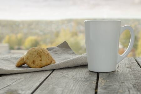 White mug on a wooden table with cookies on a linen napkin against the background of a window view in cloudy autumn weather