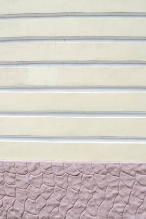 Textured yellow-pink wall with horizontal stripes and waves.