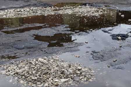 Pits and puddles covered with gravel on the roadway