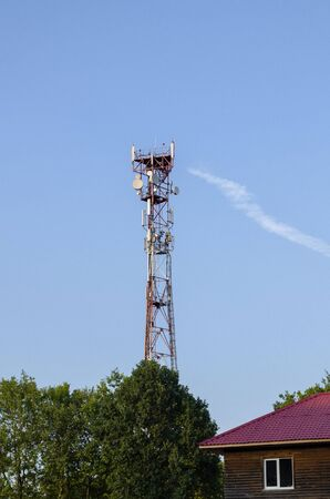 Radio Tower. Looking up at a red and white radio tower against a blue sky background