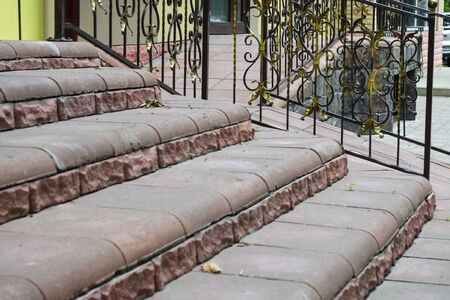 Staircase made of artificial red stone and forged railing
