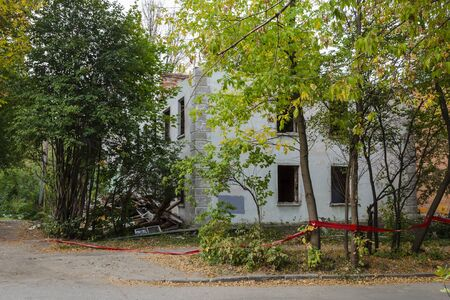 House under demolition without windows and roof. Building debris around it. Stock fotó