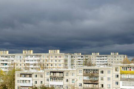 Gloomy dark rain clouds over the sunlit multi-storey panel houses