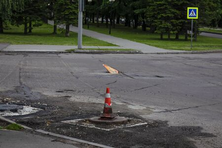 Road repair, sign in the pit, cones on protruding wells, cut off top layer of asphalt