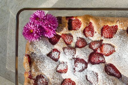 Cake with strawberries sprinkled with powdered sugar in a glass form with chrysanthemums
