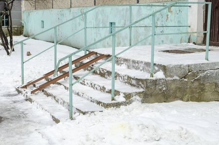 A ladder sprinkled with snow to the staircase with a railing