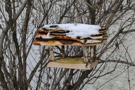 Bird feeder made of birch branches and birch bark with millet and snow poured on it on the roof