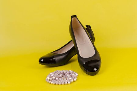 Black leather shoes with varnished noses on a low stable heel and beads on a yellow background. Stock fotó