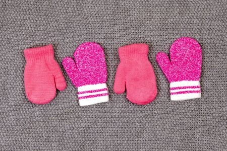 Two pairs of baby pink mittens arranged in a row on a gray knitted background