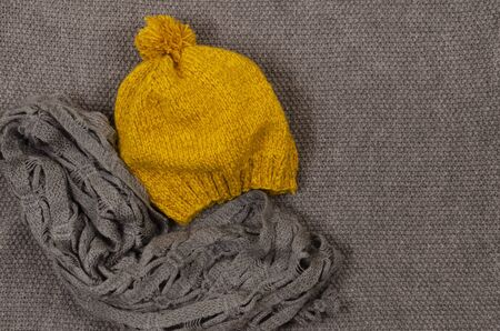 Yellow mustard beret with pampon and gray scarf on a gray knitted background