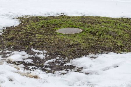 Manhole of a sewer well on a lawn with grass sprouted around it in winter snowy time Stock fotó