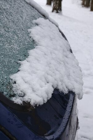 Snow falling on the rear window of a car trunk sliding from a car Stock fotó