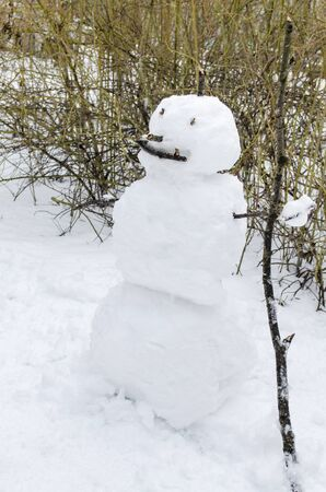 Snowman on the street with a cane from a tree branch, eyes and mouth made of sticks Stock fotó