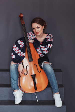 traditional dress: Photo of a beautiful female musician playing a cello. Girl in traditional dress. Woman in vyshyvanka.