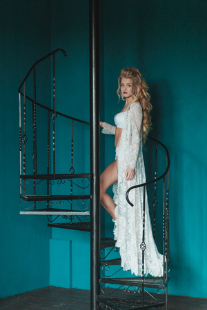 negligee: Beautiful blond bride in white negligee walking up black wrought iron staircase.