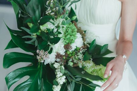 Wedding bridal bouquet with big tropical green leaves and white flowers. Stock Photo