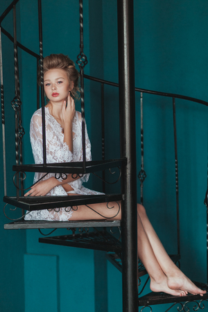 elegant staircase: Beautiful blond bride in white negligee sitting on the black wrought iron stairs Stock Photo