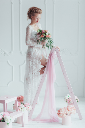Gorgeous bride with wedding bouquet standing on the decorated ladder. Look down. Stock Photo