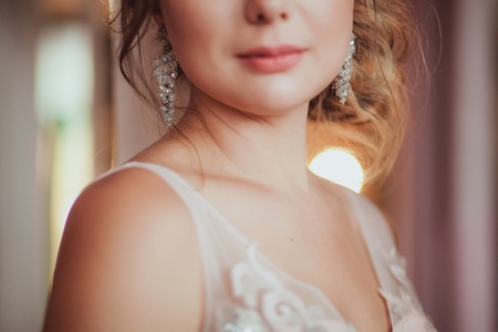 arrodillarse: romantic Woman in bridal dress with wedding bouquet standing against the light. close-up. Indoor, interior, studio.
