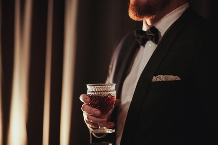 Young ginger bearded man holding a vintage glass with red wine against the light, black on background.