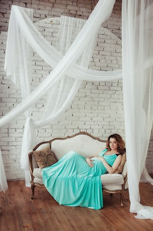 pregnant relaxing on sofa: beautiful pregnant woman in blue dress relaxing on sofa