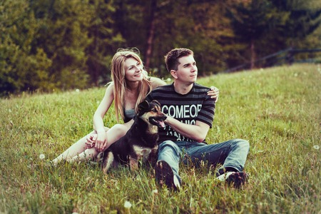 cowboy beard: Couple with a dog sitting on the grass in the forest Stock Photo