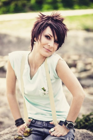 Young beautiful woman with short hair sitting on a stone Stock Photo