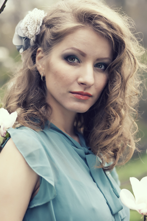 Beautiful blonde with beautiful hairstyle in vintage blue dress in a lush spring garden magnolia