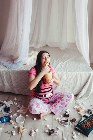 pregnant women donuts: Pretty cute pregnant woman eating ice cream Stock Photo