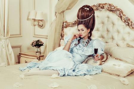 Disparo interior en el estilo de María Antonieta. Una niña sexy con un vestido retro azul exuberante con un alto peinado se encuentra en la cama con un vaso de vino espumoso en la mano. Mujer cansada de lujo Foto de archivo