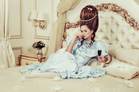 Indoors shot in the Marie Antoinette style. A young girl in a lush blue retro dress with a high hairstyle lies on the bed with a glass of sparkling wine in her hand. Woman tired of luxury Stock Photo