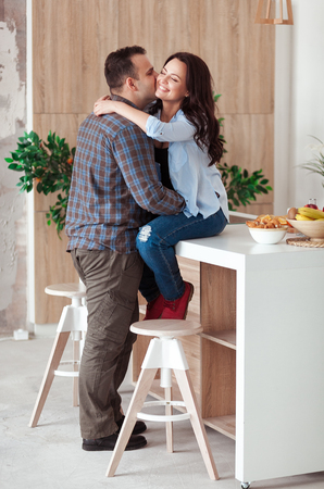 Beautiful young passionate couple is smiling and hugging before having in kitchen at home
