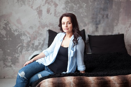 eyesclosed: Sensual woman with dark hair in blue shirt and jeans sitting on a bed at home. Loft style interior Stock Photo