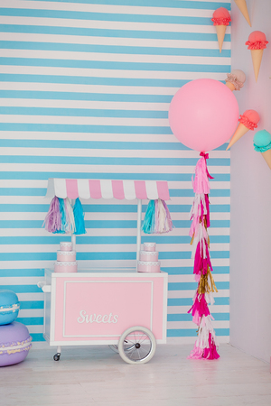 Childrens zone with sweets: lollipops, ice cream, macarons, balloon and candy bar. Children room with blue stripe background