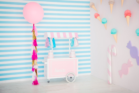 Childrens zone with sweets: lollipops, ice cream, macarons, balloon and candy bar. Children room with blue stripe background.