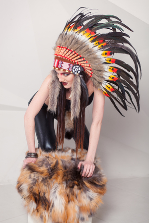 indian chief mascot: Indian woman with traditional make up and headdress looking to the side. Red Indian woman with a roach on her head
