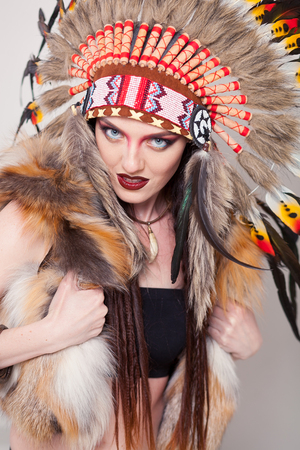 indian chief mascot: Indian woman with traditional make up and headdress looking at the camera. Redskin Indian woman on white background with a roach on her head