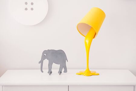A yellow lamp in the form of a bucket of paint is on a white nightstand. Nearby is a statuette of a gray elephant. In the background, the decor in the form of huge buttons Stock Photo