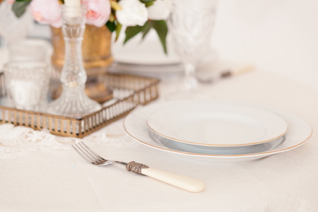 Dining table setting at Provence style, with candles, lavender, vintage crockery and cutlery, closeup. Stock Photo
