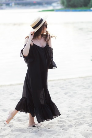 chic woman: Beautiful young brunette woman in black dress, black sunglasses and straw hat walking on the sand on the beach and posing at sunrise in summer Stock Photo